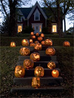 Jo-Ann's carved pumpkins line the stairs of a home in Mahone Bay in the evening.